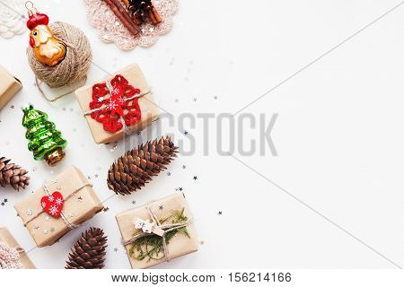 Christmas and New Year background with handmade presents wrapped in craft paper and decorations holiday symbols. Place for text.