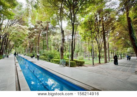ISFAHAN, IRAN - OCT 16, 2014: Women and men walking near the water ditch in a city park with green trees on October 16, 2014. Third largest city in Iran Isfahan is outstanding example of Islamic culture