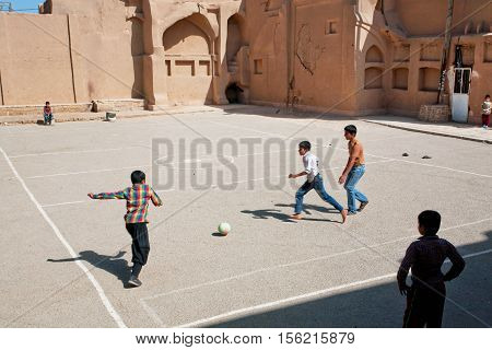 YAZD, IRAN - OCT 20, 2014: Unidentified kids running on football playground on Middle Eastern street on October 20, 2014. With population of 270.600 families Yazd is the center of Persian architecture