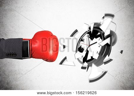 Businessman's hand in red boxing glove is smashing giant alarm clock against concrete wall. Concept of deadline.