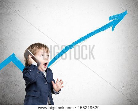 Portrait of an adorable child talking on the phone and standing in his suit near a concrete wall with a blue growing graph. Mock up