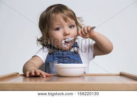 Adorable little boy eating his porridge with a small spoon. Concept of good eating habits