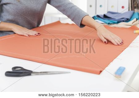 Woman's hands with red nail polish palming a piece of tissue with a pattern. Concept of sewing