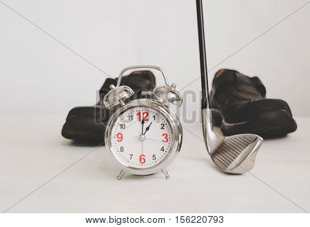 golf club and alarm clock with business leather shoes Concept of business time.