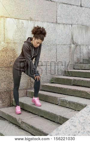 Young woman standing on stairs, taking a short break during workout outdoors
