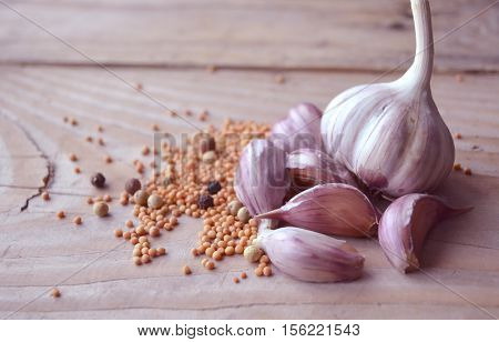 Cloves of garlic and mustard seeds on wooden board. Rustic style garlic on vintage wooden background. Fresh garlic clove. Garlic bulbs.