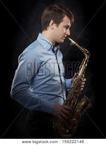 Attractive musician saxophonist with a saxophone in his hands on a dark background.