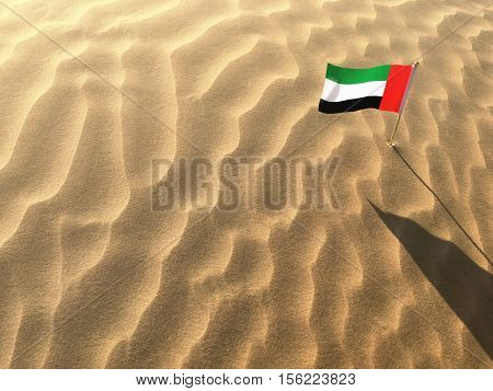 A miniature flag of United Arab Emirates flying on a sand dune. UAE celebrates it's national day on December 2.