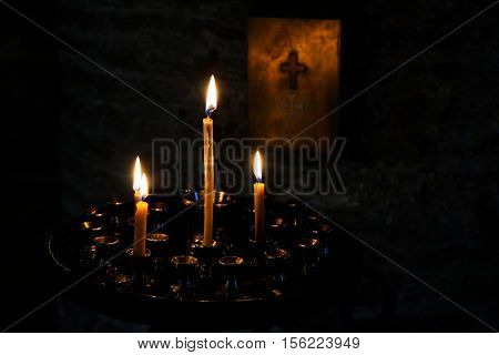 Candles burning over dark background in a church