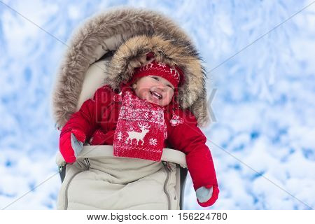 Baby In Stroller In Winter Park With Snow