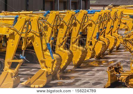 New industrial excavator earthwork machines hydraulic arms steel scoop buckets closeup abstract.