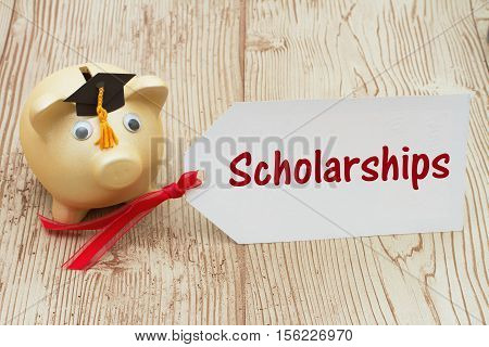 Getting a educational scholarship A golden piggy bank and grad cap on a desk with a gift tag with text Scholarships