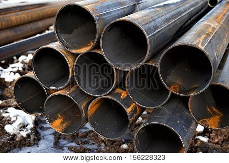 New steel pipes with rust lay on a construction site