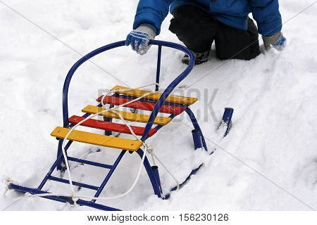 Walking outdoors in the winter time. The child sits on his haunches in the snow and rolls colorful sleds.