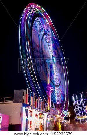 Ferris wheel shoot at night while rotating at the fair in Antwerpen Belgium. The lights draw a colourful circle.
