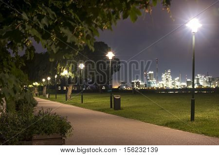 Night photo of the park next to the river with the lights of the Antwerpen port on the background