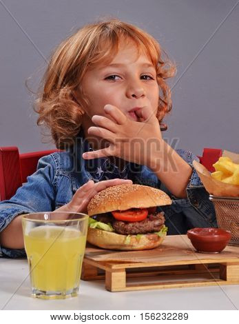 Funny kid eating burger sucking finger and drinking orange soda.
