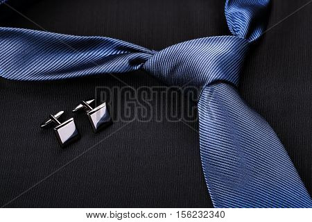 blue tie and cufflinks on dark suit