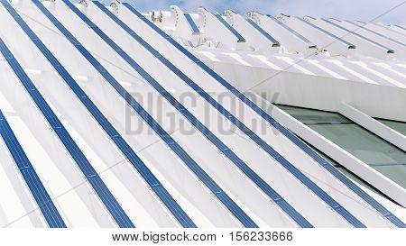 Facade of modern contemporary white building with a lot of blue photovoltaic plates on it Rio de Janeiro Brazil