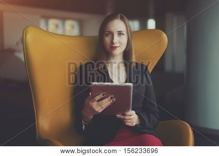Portrait of young successful woman entrepreneur in a red dress and jacket sitting on orange armchair and working on her digital tablet office interior