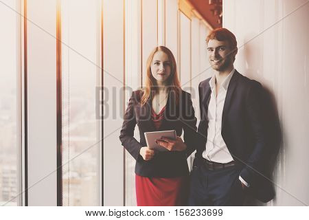 Group of business in office interior standing between window and column: smiling elegant man in formal suit and his female colleague in red dress and jacket holding tablet