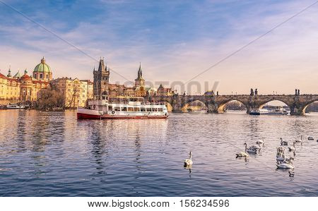 Prague cityscape with Vltava and Charles Bridge - Landscape with the Vltava river the famous Charles Bridge with swans and boats floating on the river. Picture taken in Prague Czech Republic.