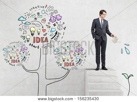 Businessman in glasses is watering a sketch of a plant while standing on stairs near concrete wall with business idea trea.