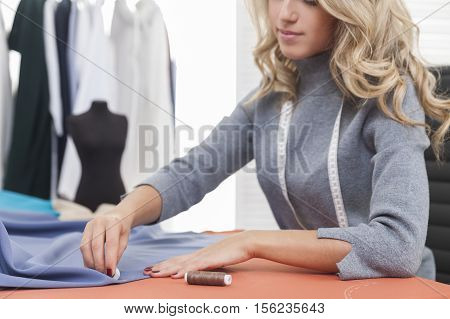 Woman Drawing A Pattern On Blue Material