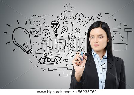 Close up of black haired woman drawing a business idea sketch on a glassboard. Gray wall is in the background