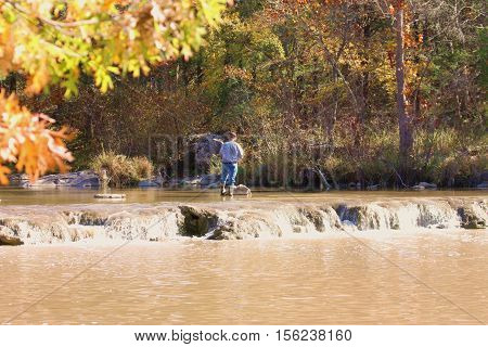 An older man, facing away, wearing blue jeans, blue plaid shirt and wading shoes, is standing in the Blue River of Oklahoma, fly fishing in fall. Trees with fall colors in background and autumn leaves and small waterfall is in foreground.