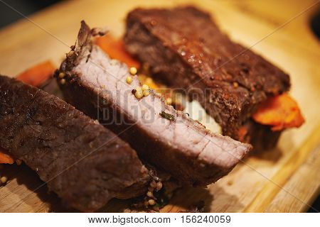 roasted beef with vegetables on wooden table. shallow doff