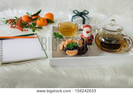 Green mint tea chocolate mandarin slices and Santa Claus on tray near notebook pencils mandarins mountain ash on white artificial fur background. Time break notebook surprise preparation.