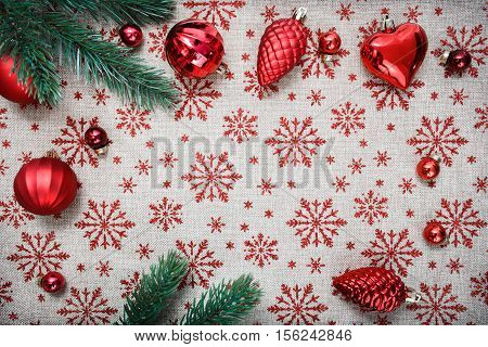 Red Christmas ornaments and xmas tree on canvas background with red glitter snowflakes. Xmas card. Happy New Year. Space for text