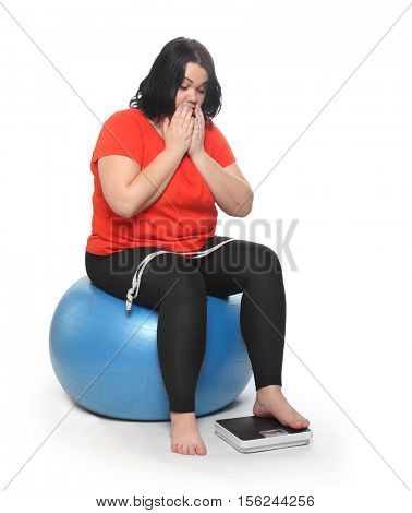 Depressed woman with measure tape and weighing machine sitting on white background. Dieting and slimming theme.