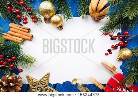 Christmas border with fir tree branches, cones, christmas decorations on blue wooden boards ready for your design