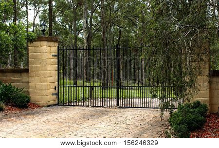 Black wrought iron driveway entrance gates set in brick fence