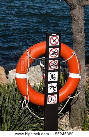 Red life buoy preserver situated on banks of harbour