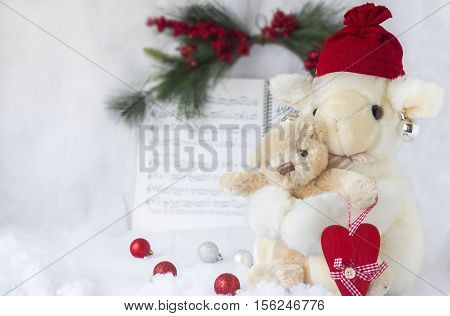 horizontal christmas image of toy stuffed lamb holding  small toy baby bear holding a red heart  facing camera scattered with balls with green fern and music book in background on white background.