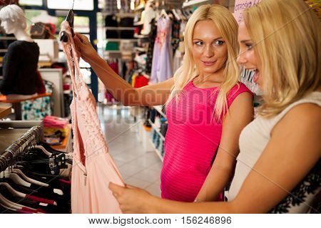 Shopping in clothes store - Two cute women in clothing shop picking garment