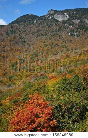 granite cliffs atop a hillside covered in autumn foliage