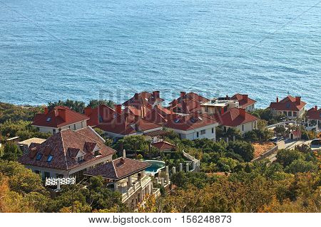 Cottage village with red roofs on the hillside against the backdrop of the sea. Quiet location on the sea or ocean. Calm sea bright sunny day. Villas in the woods. House in the woods or park. Detached villa with pool on the hillside. Top view of the house