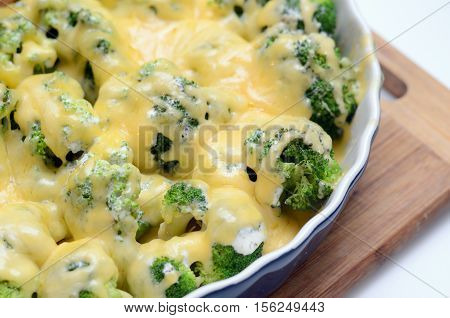 millet casserole with broccoli and cheese in ceramic dish. Close-up and selective focus