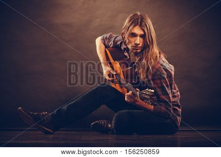 Hobby music concept. Romantic young man with guitar. Boy is sitting on the floor and playing the instrument.