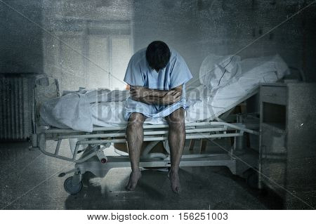 young desperate man sitting at hospital bed alone sad and devastated suffering depression crying at clinic for serious disease diagnose worried in fear on grunge dirty background