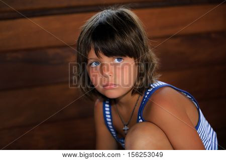 amazing closeup view of pretty beautiful upset bored little girl portrait against brown wooden background