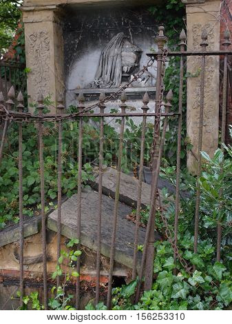 A busted up old tomb overgrown with vines and surrounded by a broken down rusted fence.
