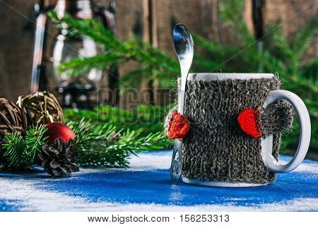 Mug with woolen warmer holding teaspoon on the table with christmas decorations