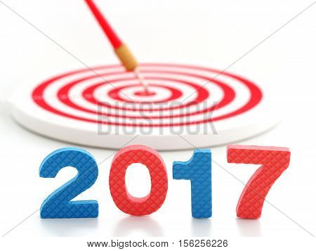Year 2017 goal two thousand seventeen with blur red bullseye dart arrow hitting target center dartboard in background. Happy New Year.Year