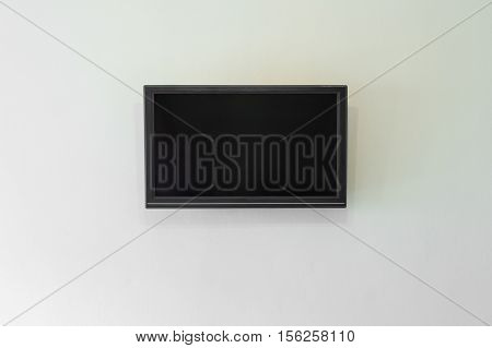 Black LCD or LED tv screen hanging on a wall background