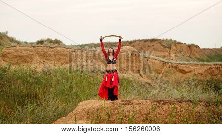 Passionate dance with a sword. Tribal style. Attractive girl in costume dancing outdoors. Sand dunes. Nomads. Oriental beauty